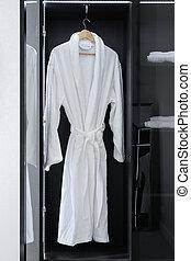 White bathrobe hanging in the closet