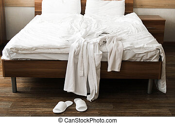White bathrobe over bed in hotel room with slippers. Hospital room