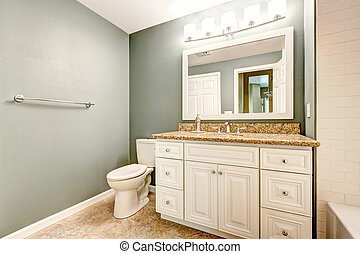 White bathroom vanity cabinet with granite top and mirror....
