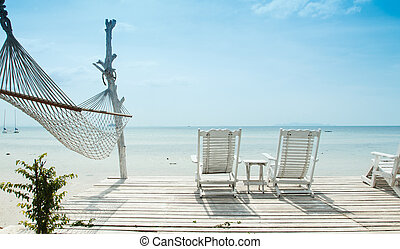 white beach chair and hammock facing ocean