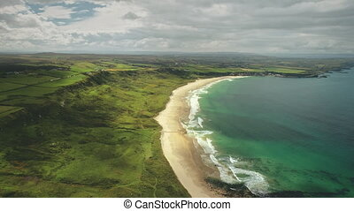 White Beach sand coast aerial zooming, Antrim County, Nortern Ireland. Epic landscape of greenness cliff shore of Atlantic ocean bay. Calm water at dusk cloudy day. Footage shooting shot in 4K, UHD