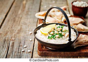 white beans hummus with lemon on dark wood background....