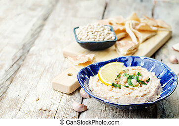 white beans hummus with lemon on white wood background....