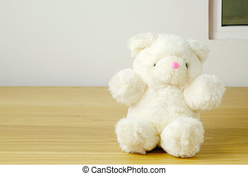 white bear doll sit on wood table and window background