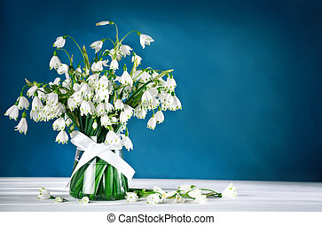 White beautiful flowers Loddon Lily stand in a glass vase on white wooden boards.
