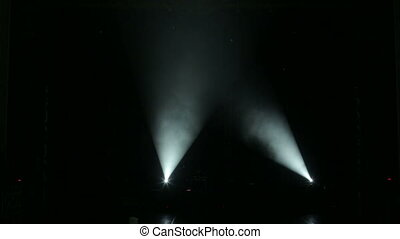 White rays in the dark on an empty stage.