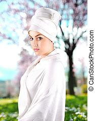 White beautiful woman wearing sari and standing in garden