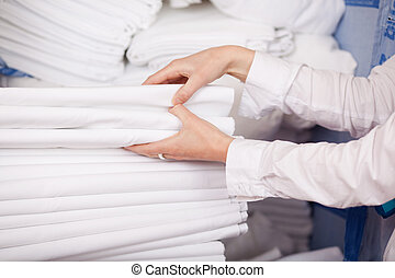 White Bedsheets Stacked In Stock Room - Closeup of white...