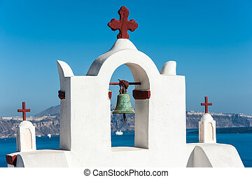 White bell tower with red cross in Santorini