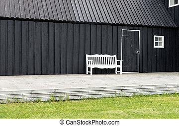 White bench in front of black wooden house