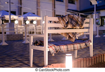 White Bench with Plaid Blankets on Patio at Dusk