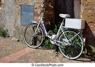 White bicycle leaning against a wall in Pienza