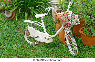 White bicycle with bouquet of flower in a garden