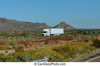 White big rig American long haul semi truck with moving on wide divided turning highway with mountain