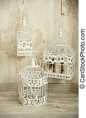 White birdcages in the interior wall with an ornament.