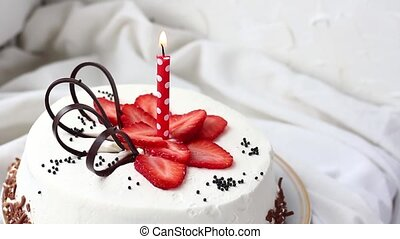 white birthday cake with strawberries and one candle closeup...