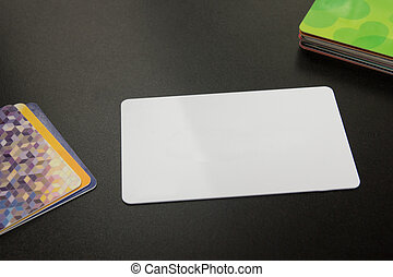 White blank business card. Office desk with set of colorful supplies, cup, pen, pencils, flower, notes, cards on black board table background. Top view and copy space for ad text