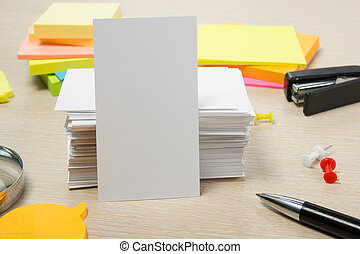 White blank business card. Office table desk with set of colorful supplies, cup, pen, pencils, flower, notes, cards on beige background. Top view and copy space for ad text