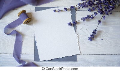 White blank card, envelope and ribbon on a background of pink and blue fabric with lavender flowers on a white background. Mockup with envelope and blank card. Flat lay. Top view.