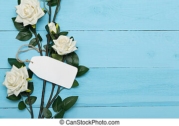 white blank card with flowers on a wooden blue background
