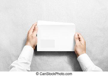White blank envelope mock up holding in hand. Empty letter...