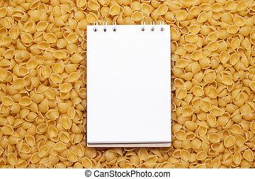 blank notepad on uncooked macaroni background - white blank...