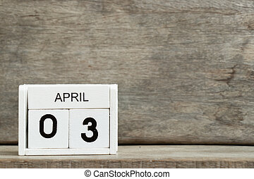 White block calendar present date 3 and month April on wood background