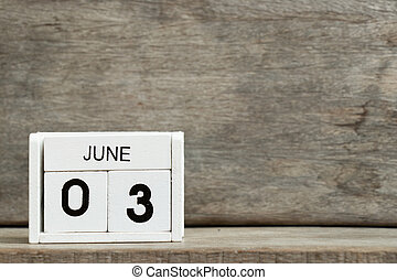 White block calendar present date 3 and month June on wood background