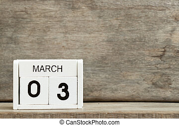White block calendar present date 3 and month March on wood background