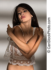 Tall slender nude brunette in a sheer white blouse
