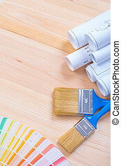 white blueprints color sampler and two paintbrushes with blue ha