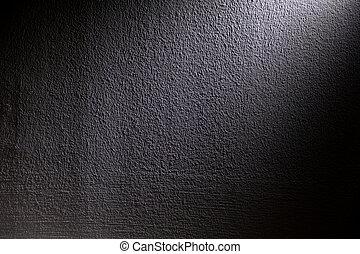 White, blur spotlight effect on black background. Concrete wall.