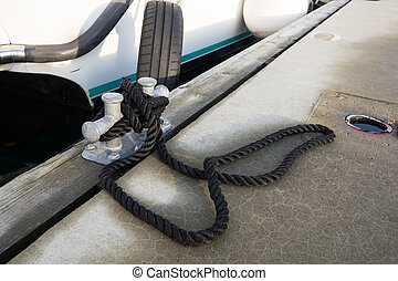 White boat tied to the pier with a black rope