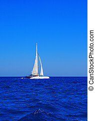 White boat with sails in the Mediterranean