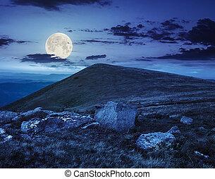 white boulders on the hillside at night - composit landscape...