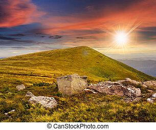 white boulders on the hillside at sunset - composit...