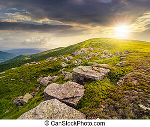 white boulders on the hillside at sunset - landscape with...