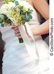 white bouquet in hands of the bride
