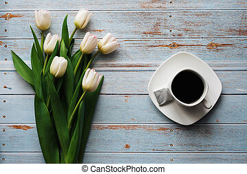 White bouquet of tulips on a wooden blue background with a Cup of coffee