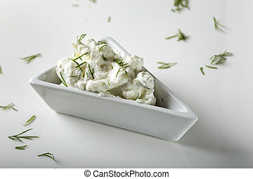 White bowl filled with cheese cream with dill on plate