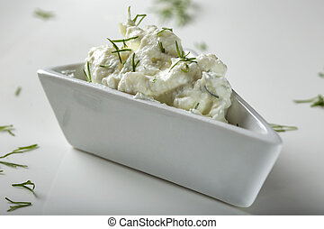 White bowl filled with cheese cream with dill