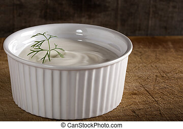 White bowl filled with sour cream on wood