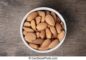 white bowl full of almonds, on wooden table