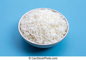 White bowl of rice on blue background.