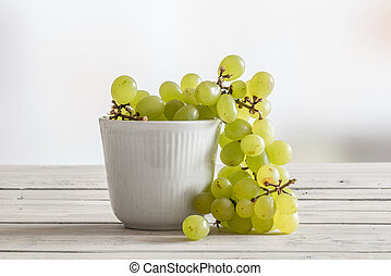 White bowl with green grapes on a wooden table