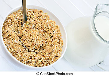 White bowl with oat flakes and milk on table