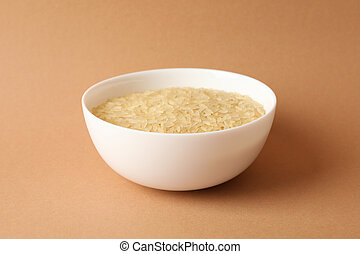 White bowl with rice on craft background, close up