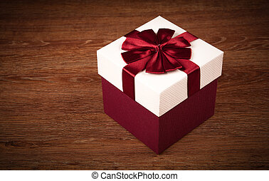 white box with red bow on a wooden background