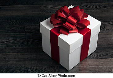 white box with red bow on a wooden table on a black background