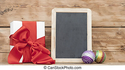 White boxs, red ribbon, christmas ball and blank small blackboard on wood background